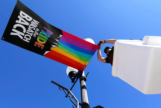 Justin Motley repairs Pride flags hanging in Heber, Utah on Monday, June 10, 2019. The flags have caused a stir in the 15,000-person town and beyond, drawing attention at a Heber City Council meeting, on social media and from the American Civil Liberties Union of Utah. Some of the discussion has revolved around the flags' message itself. But the controversy has also raised broader questions for the city about whether,  and how, to determine what kind of content can be publicly displayed on city property. (Kristin Murphy/The Deseret News via AP)