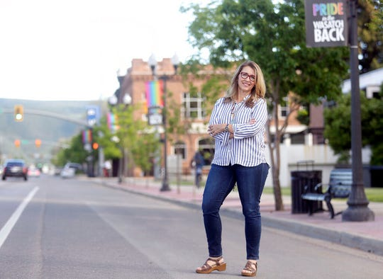 Heber City Mayor Kelleen Potter poses for a portrait in front of pride flags hanging on Main Street in Heber City, Utah,  on Monday, June 10, 2019. The flags have caused a stir in the 15,000-person town and beyond, drawing attention at a Heber City Council meeting, on social media and from the American Civil Liberties Union of Utah. Some of the discussion has revolved around the flags' message itself. But the controversy has also raised broader questions for the city about whether,  and how, to determine what kind of content can be publicly displayed on city property. (Kristin Murphy/The Deseret News via AP)