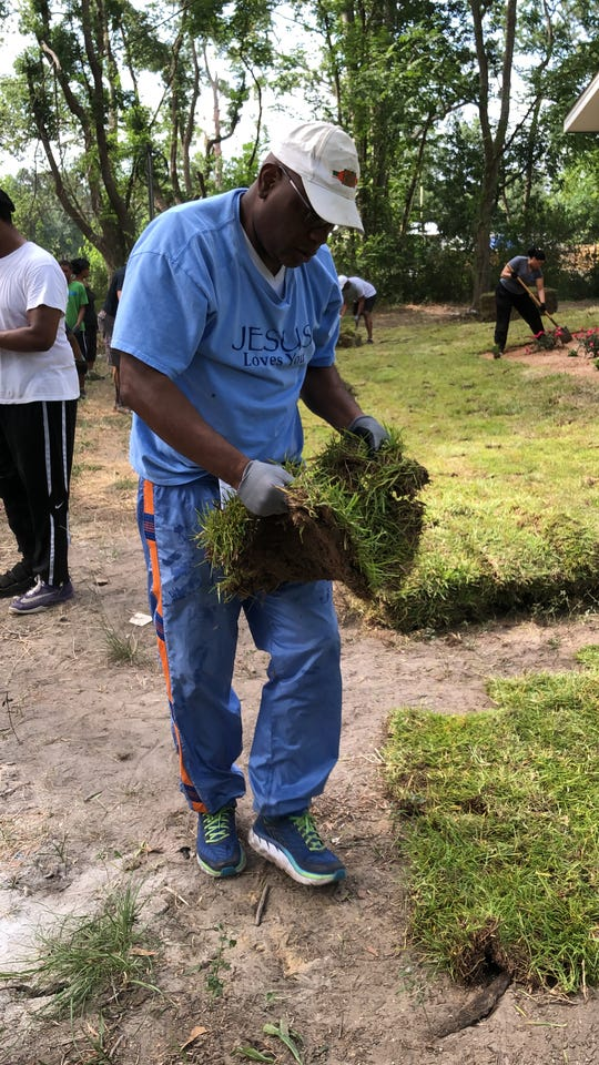 Bethel Missionary Baptist Pastor R.B. Holmes places sod at the new home in Gadsden County.