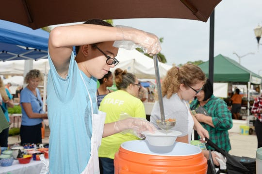 Volunteer A.J. Williams serves chicken soup at Treasure Coast Food Bank's Empty Bowls event in downtown Fort Pierce.