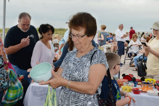 Julie Carrozzella checks out a bowl at Treasure Coast Food Bank's Empty Bowls event in downtown Fort Pierce.