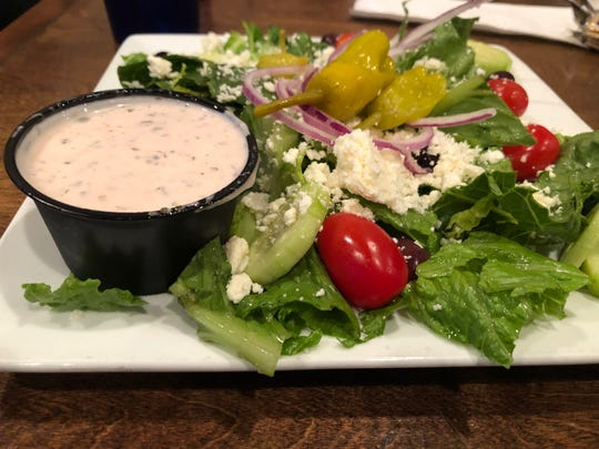 Spiro's Taverna's Greek salad is made with crispy romaine lettuce, fresh tomatoes, cucumbers, olives, peperoncini, and feta served with a creamy Greek dressing.