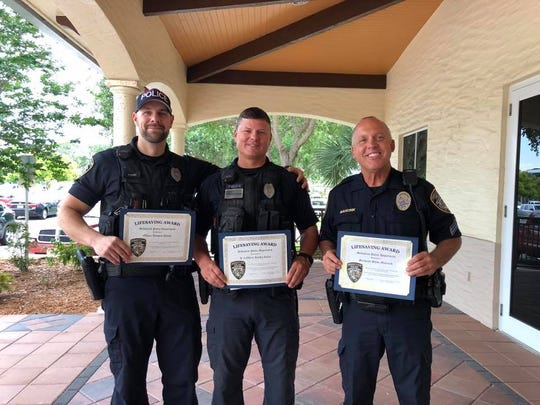 Officer Thomas Quinn (right), Cpl. Ritchie Revis (center), and Sgt. Steve Marcinik (right) were honored Wednesday with lifesaving awards for pulling a man from a burning home in February.
