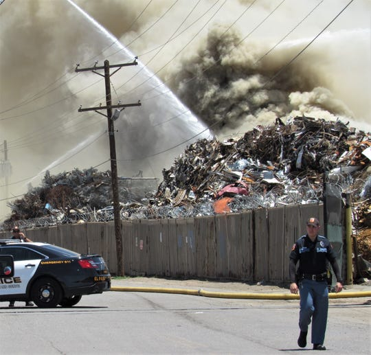 A police officer walks by as firefighters Friday afternoon, June 14, 2019, battled a blaze at the W. Silver Recycling plant in Central El Paso.