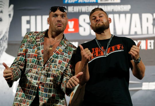 Tyson Fury, left, of England, and Tom Schwarz, of Germany, pose for photographers during a news conference for their upcoming fight Wednesday, June 12, 2019, in Las Vegas. The two are scheduled to fight in a heavyweight bout Saturday in Las Vegas.
