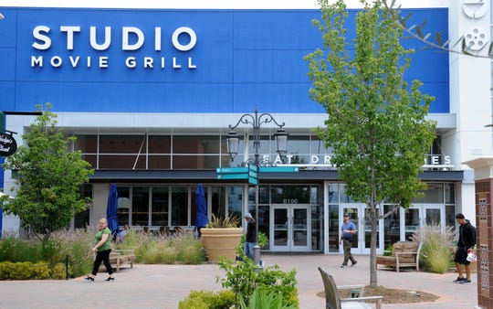 Customers walk past the Studio Movie Grill at the Simi Valley Town Center.