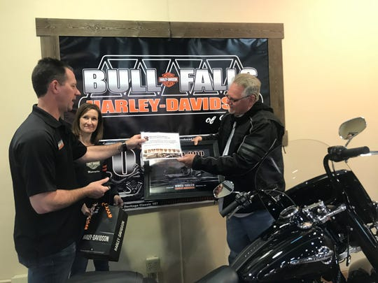 Owners of the Wausau Harley-Davidson dealership, Erik Vandervest and Dixie Kinnard, present Wayne Bartlett with gifts for having purchased the 5 millionth bike manufactured by the iconic Wisconsin motorcycle brand.