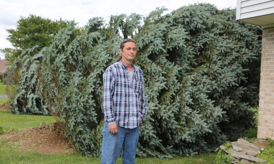 Bill Robinson stands in front of one of his trees that was blown over during a storm Thursday night.  Several trees in the Pine Valley Farms neighborhood were also damaged.