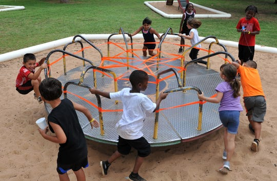 A group of kids plays games on a mary-go-round during the Camp Fire of North Texas second week of Camp Fire Day Camp at Harrell Park.