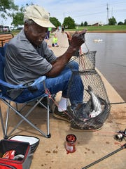 Clemmie Smith shows his catch of channel catfish while fishing Friday morning at the South Weeks Park pond.