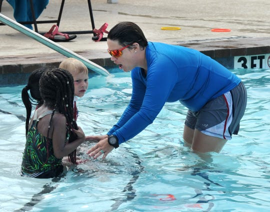 Camp Fire of North Texas, pool director/lifeguard Tiffany Self works with a small group of kids during one of the camp's swimming lessons Friday afternoon.