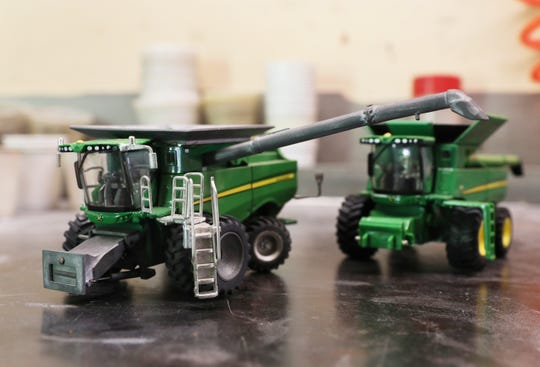 A combine with custom parts added next to a stock combine toy. The gray pieces are cast at Moore's Farm Toy's facility near Trinway.