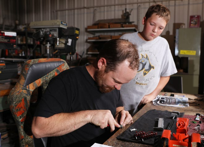 Coner Maxwell, 11, watches his father Blair build a part at Moore's Farm Toys' facility near Trinway. The elder Maxwell works with his father-in-law Jeff Moore at Moore's Farm Toys.