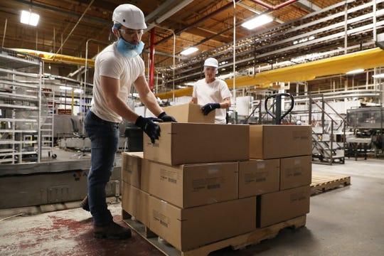 Tanner Bryan, left, and Brady Insley put boxes of buns on a pallet at Bimbo's Airport Road bun factory. Bimbo begins hiring seasonal help in April.