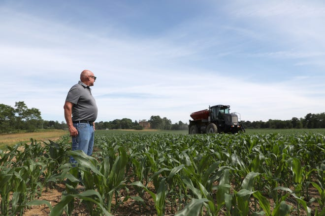 Steve Little watches as a contractor spreads nitrogen on one of his corn fields near Trinway. Because heavy rains this spring, Little estimates his harvest will be only about 80% of last year, but Muskingum County still fared better than much of the rest of the state during planting season.