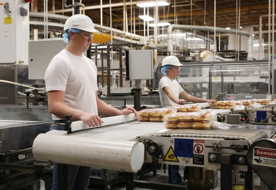 Ben Shaeffer keeps an eye on packages of buns as they roll out of a machine at Bimbo's Airport Road facility.