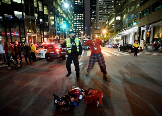 A police officer and a Raptors fan dance in the streets.