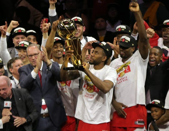 Raptors forward Kawhi Leonard lifts the Larry O'Brien Championship Trophy after beating the Warriors.
