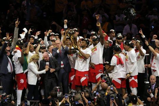 Raptors forward Kawhi Leonard lifts the Larry O'Brien Championship Trophy after beating the Warriors.