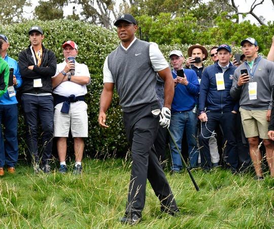 Tiger Woods moves to the fifth green after leaving the gallery in the first round.