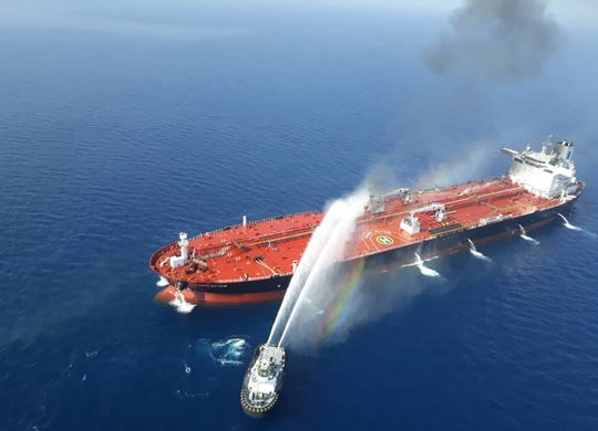A picture obtained by AFP from Iranian news agency Tasnim on June 13, 2019 reportedly shows an Iranian navy boat trying to control fire from Norwegian owned Front Altair tanker said to have been attacked in the waters of the Gulf of Oman.