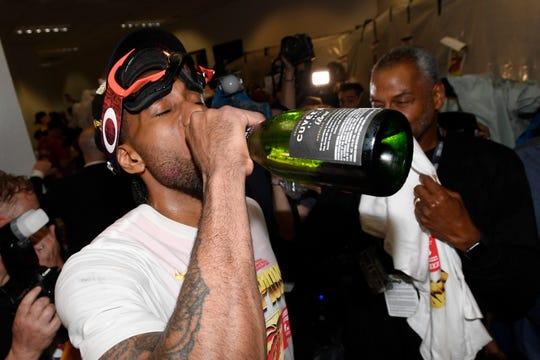 Kawhi Leonard drinks champagne as he celebrates.