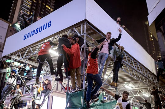 Raptors supporters climb a scaffold as fans celebrate in the streets.