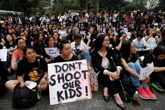 Hundreds of mothers protest against the amendments to the extradition law after Wednesday's violent protest in Hong Kong on Friday, June 14, 2019. Calm appeared to have returned to Hong Kong after days of protests by students and human rights activists opposed to a bill that would allow suspects to be tried in mainland Chinese courts. (AP Photo/Vincent Yu) ORG XMIT: XVY402