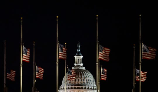 The U.S. Capitol Dome is seen beyond American Flags around the the base of the Washington Monument in Washington, early Saturday, Dec. 22, 2018. The American Flags are at half-staff to honor of former President George H.W. Bush. Hundreds of thousands of federal workers faced a partial government shutdown early Saturday after Democrats refused to meet President Donald Trump's demands for $5 billion to start erecting a border wall with Mexico. Overall, more than 800,000 federal employees would see their jobs disrupted, including more than half who would be forced to continue working without pay. (AP Photo/Carolyn Kaster) ORG XMIT: DCCK103