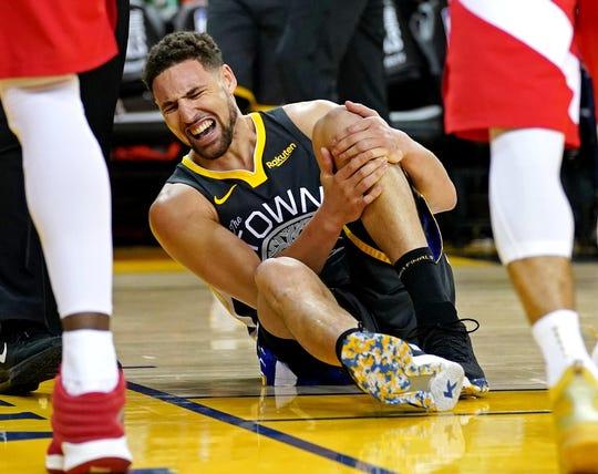 Klay Thompson clutches his left knee.