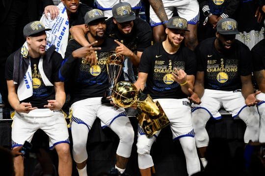 Klay Thompson (left), Kevin Durant (middle) and Stephen Curry (right) celebrate after defeating the Cleveland Cavaliers in the 2018 NBA Finals.