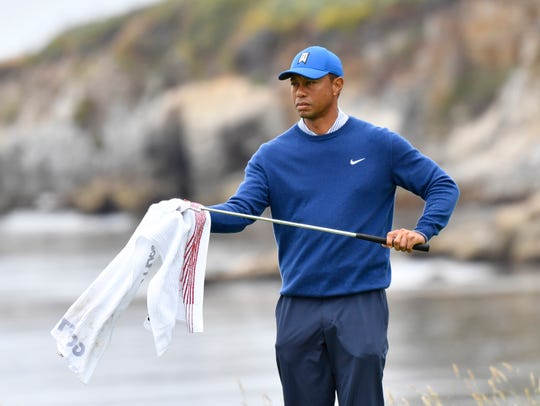 Tiger Woods wipes down a club on the 18th hole during the second round of the 2019 U.S. Open.