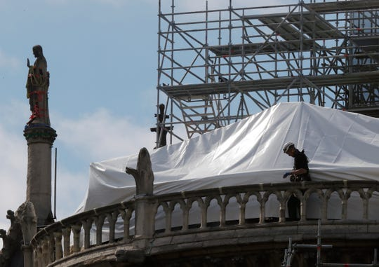 A worker checks the waterproof tarps on Notre Dame cathedral in Paris.