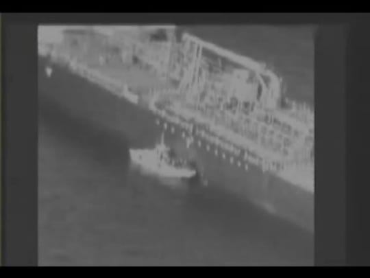 A frame grab from a handout video made available by the U.S. Central Command shows a smaller boat near to what appears to be the vessel Kokuka Courageous, in the Gulf of Oman, on June 13, 2019. According to the US Navy, the video allegedly shows an Iranian Gashti Class patrol boat's crew 'removing an unexploded limpet mine' from the Kokuka Courageous tanker.