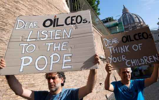Activists hold up signs outside the Vatican as Pope Francis meets with oil executives, Friday, June 14, 2019.