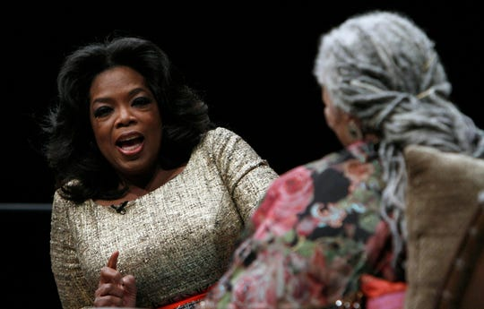 Oprah Winfrey talks with author Toni Morrison at an awards dinner in 2010.