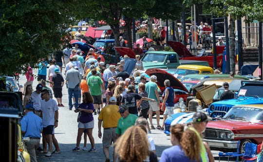 A crowd walks by some of 300 cars shown during the Father's Day Main Street 20th Anniversary 2019 Car Show in downtown Anderson Saturday, June 15, 2019.