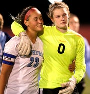 St. Mary Catholic's Abbi Thelen (23) and goalie Greta Norville comfort each other after losing in sudden death penalty kicks against Oostburg during their WIAA Division 4 semifinal girls state soccer game Friday at Uihlein Soccer Park in Milwaukee.