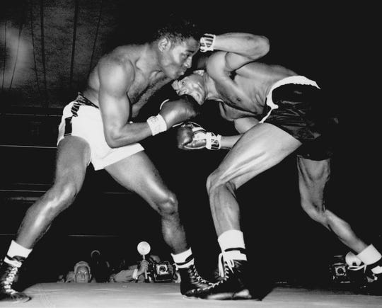 Ezzard Charles gets Johnny Holman's attention with a right to the jaw during a bout at Music Hall in 1955. Charles won.