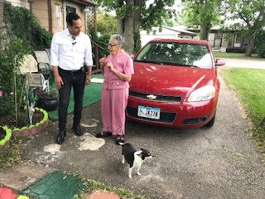 Julián Castro talks with Arletta Swain outside of her mobile home in Waukee.