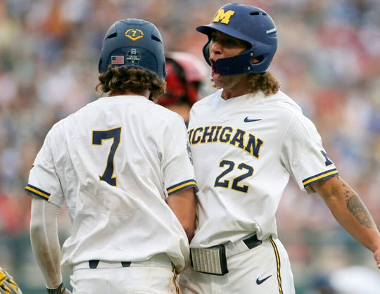 Michigan's Jesse Franklin, left, and Jordan Brewer celebrate after scoring on Jimmy Kerr's two-run triple against Texas Tech in the third inning of the College World Series game on Saturday, June 15, 2019, in Omaha, Nebraska.