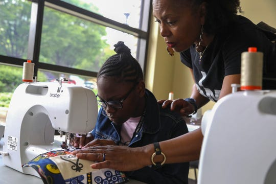(L to R) Epiphany Bryant, 13 of St. Paul, Minnesota gets help and encouragement from April Shipp of Rochester Hills during Juneteenth celebrations and events inside of the Charles H. Wright Museum of African American History in Detroit, Michigan on Saturday, June 15, 2019.