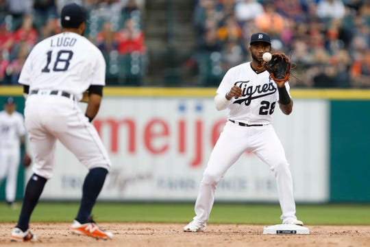 Dawel Lugo tosses the ball to shortstop Niko Goodrum (28) for the out at second base against the Indians at Comerica Park on Saturday.