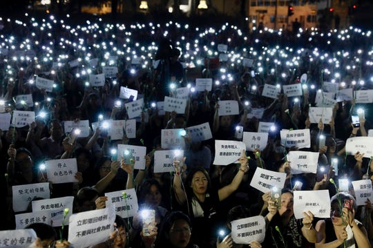 """Hundreds of mothers holding placards, some of which read """"If we lose the young generation, what's left of Hong Kong"""", and lit smartphones protest against the amendments to the extradition law in Hong Kong on Friday, June 14, 2019."""