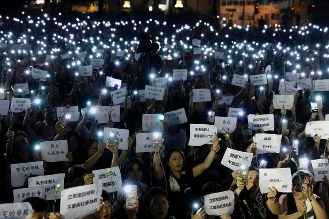 "Hundreds of mothers holding placards, some of which read ""If we lose the young generation, what's left of Hong Kong"", and lit smartphones protest against the amendments to the extradition law in Hong Kong on Friday, June 14, 2019."