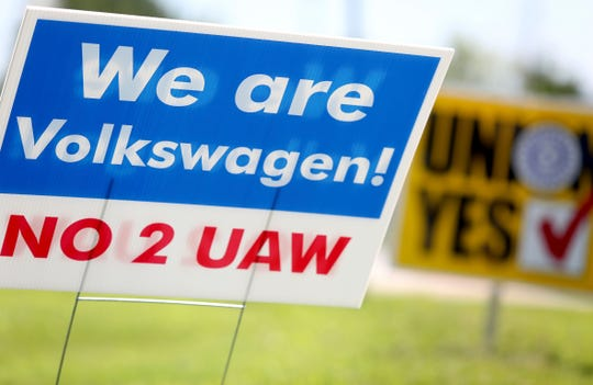 Signs for and against unionization are in a roundabout along Volkswagen Drive in front of the Volkswagen plant Friday, June 14, 2019 in Chattanooga, Tenn..