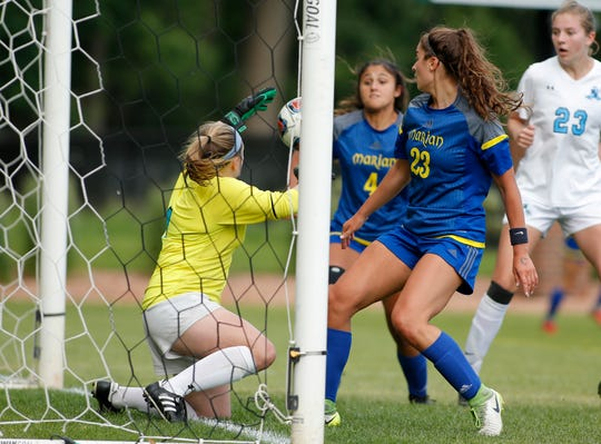 Forest Hills Northern goalkeeper Parker Hutchinson, left, blocks a shot but doesn't secure the ball, allowing a rebound goal in overtime for Bloomfield HIlls Marian's Maria Askounis (4).