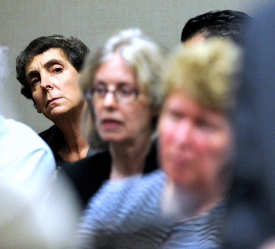 From left, Defendants Liane Shekter-Smith, Corrine Miller, and   Nancy Peeler listen to their defense attorneys.  Defense attorneys and special prosecutors for six individuals charged in the Flint Water Crisis stand in front of 67th District Court Judge Tracy Collier-Nix during a brief hearing, Tuesday morning, August 9, 2016.