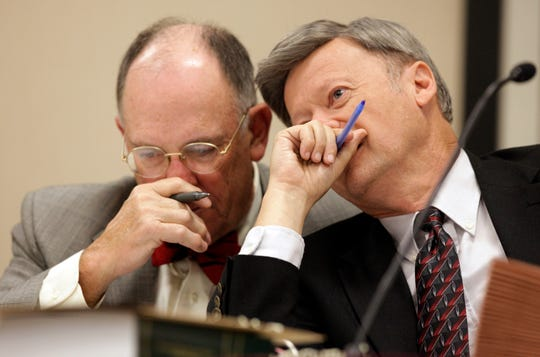 In this Oct. 26, 2009, file pool photo, Larry Leake, right, State Board of Elections Chairman, right, speaks with board member Robert Cordle during board's hearing on in Raleigh, N.C.