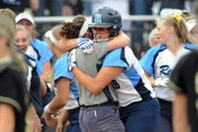Warren Regina's Adriana James, right, is hugged by team personnel after her winning hit in the bottom of the eighth.